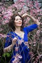 Portrait of a middle-aged brunette in a blue dress next to a cherry blossom Royalty Free Stock Photo