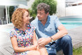 Portrait of middle aged couple sitting outside the house Royalty Free Stock Photo