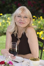Portrait of middle aged woman with red wine outdoors a smiling sitting at the outdoor table Royalty Free Stock Photo