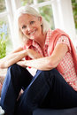 Portrait of middle aged woman sitting on window seat looking to camera smiling Stock Photography