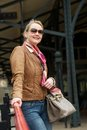 Portrait of middle aged woman smiling outdoors a beautiful with sunglasses and bag Stock Photos