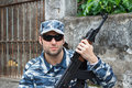 Portrait of military caucasian man in urban warfare holding rifl with black sunglasses rifle Royalty Free Stock Photos