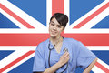 Portrait of mixed race female surgeon standing over british flag Stock Photography