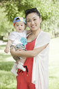 Portrait of mother and baby an asian is smiling holding her on grass Royalty Free Stock Photos