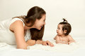 Portrait of mother and baby having fun, lie on white, yellow toned Royalty Free Stock Photo