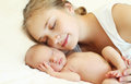 Portrait of mother and baby sleep together on the bed Royalty Free Stock Photo