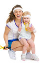Portrait of mother and baby in tennis clothes holding medal isolated on white Royalty Free Stock Photo