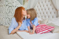 Portrait of mother kiss her little daughter in bedroom Royalty Free Stock Photo