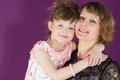 Portrait of a mother and young daughter in a purple room the hugging Royalty Free Stock Images
