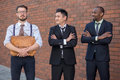 Portrait of multi ethnic business team three smiling men standing against the background red brick wall the one men is european Royalty Free Stock Images