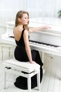 Portrait of musician sitting and playing piano woman in black dress concept music arts Stock Photography