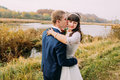 Portrait of newlywed young couple outdoors. Groom kissing his charming bride in cheek on riverside Royalty Free Stock Photo
