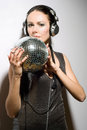 Portrait of nice young brunette in headphones with a mirror ball Royalty Free Stock Photography