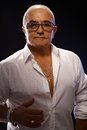 Portrait of old playboy in white shirt and lots gold jewels Royalty Free Stock Photography