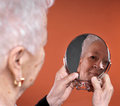 Portrait of old woman looking into a mirror Royalty Free Stock Photo