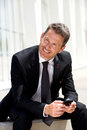 Portrait of businessman sitting and smiling holding mobile phone Royalty Free Stock Photo