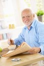 Portrait of older man at breakfast table happy having cereal reading papers smiling camera Royalty Free Stock Images