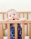 Portrait of one cute adorable funny baby of nine months standing in bed crib chewing eating sucking wooden sides Royalty Free Stock Photo