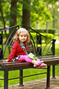 Portrait of a one year old cute little curly girl wearing red cardigan and a headband with a bowl sitting on a bench in the park Royalty Free Stock Photo