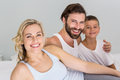 Portrait of parents and son sitting on bed in bedroom Royalty Free Stock Photo