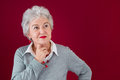 Portrait of pensive elderly woman with a red background Royalty Free Stock Photo