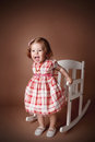 Portrait of a playful amd happy little girl pretty baby in rocking chair Stock Photography