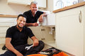 Portrait of plumber with apprentice in domestic kitchen Stock Images