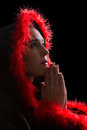 Portrait of praying woman in black cape and red fringe sad with feather Stock Images