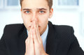 Portrait of praying young businessman closeup sad in office Royalty Free Stock Images