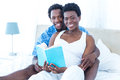 Portrait of pregnant woman and her husband reading book women at home Stock Photos