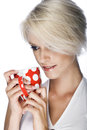 Portrait of a pretty blond woman daydreaming with short hair while holding red mug Royalty Free Stock Photo