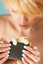 Portrait of a pretty blond young woman smelling flowers in flowerpot focus on manicure and Stock Photography