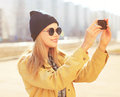 Portrait pretty blonde makes selfie portrait on the smartphone carefree hipster girl wearing a black sunglasses and hat enjoying Royalty Free Stock Photography