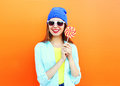 Portrait pretty cool smiling woman and lollipop over colorful orange Royalty Free Stock Photo