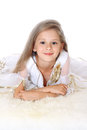 Portrait pretty little girl lying on fur and smiling isolated Royalty Free Stock Photo