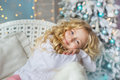 Portrait of pretty little girl sits and dreams on a chair in Christmas time Royalty Free Stock Photo