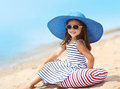 Portrait of pretty little girl in a striped dress and straw hat