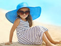 Portrait of pretty little girl in a striped dress and straw hat relaxing resting on the beach near sea Royalty Free Stock Photo