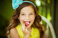 Portrait of a pretty little girl in yellow dress eats a big strawberry  with a cream Royalty Free Stock Photo