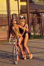 Portrait of pretty sexy young women in swimsuits with bicycle outdoors Stock Image