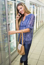 Portrait of a pretty smiling blonde woman buying frozen products and phoning at supermarket Royalty Free Stock Photo