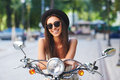 Portrait of pretty smiling girl on scooter Royalty Free Stock Photo