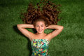 Portrait of pretty smiling young woman, laying on the grass Royalty Free Stock Photo