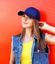 Portrait of pretty stylish young girl wearing a cap and jeans Royalty Free Stock Photo