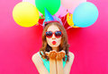 Portrait pretty woman in a birthday cap is sends an air kiss holds an air colorful balloons on pink background Royalty Free Stock Photo