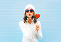 Portrait pretty woman blowing red lips sends air kiss holds lollipop heart wearing a heart shape sunglasses, knitted hat Royalty Free Stock Photo