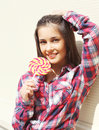 Portrait of pretty young smiling girl with sweet lollipop in summer day Royalty Free Stock Photo