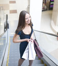 Portrait of pretty young woman with bags in the shop close up Royalty Free Stock Photo