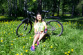 Portrait of pretty young woman with bicycle in a park - outdoor. girl sitting on the grass and drinks water from a Royalty Free Stock Photo