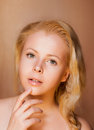 Portrait of Pretty Young Woman Blonde touching her Fresh Face Royalty Free Stock Image